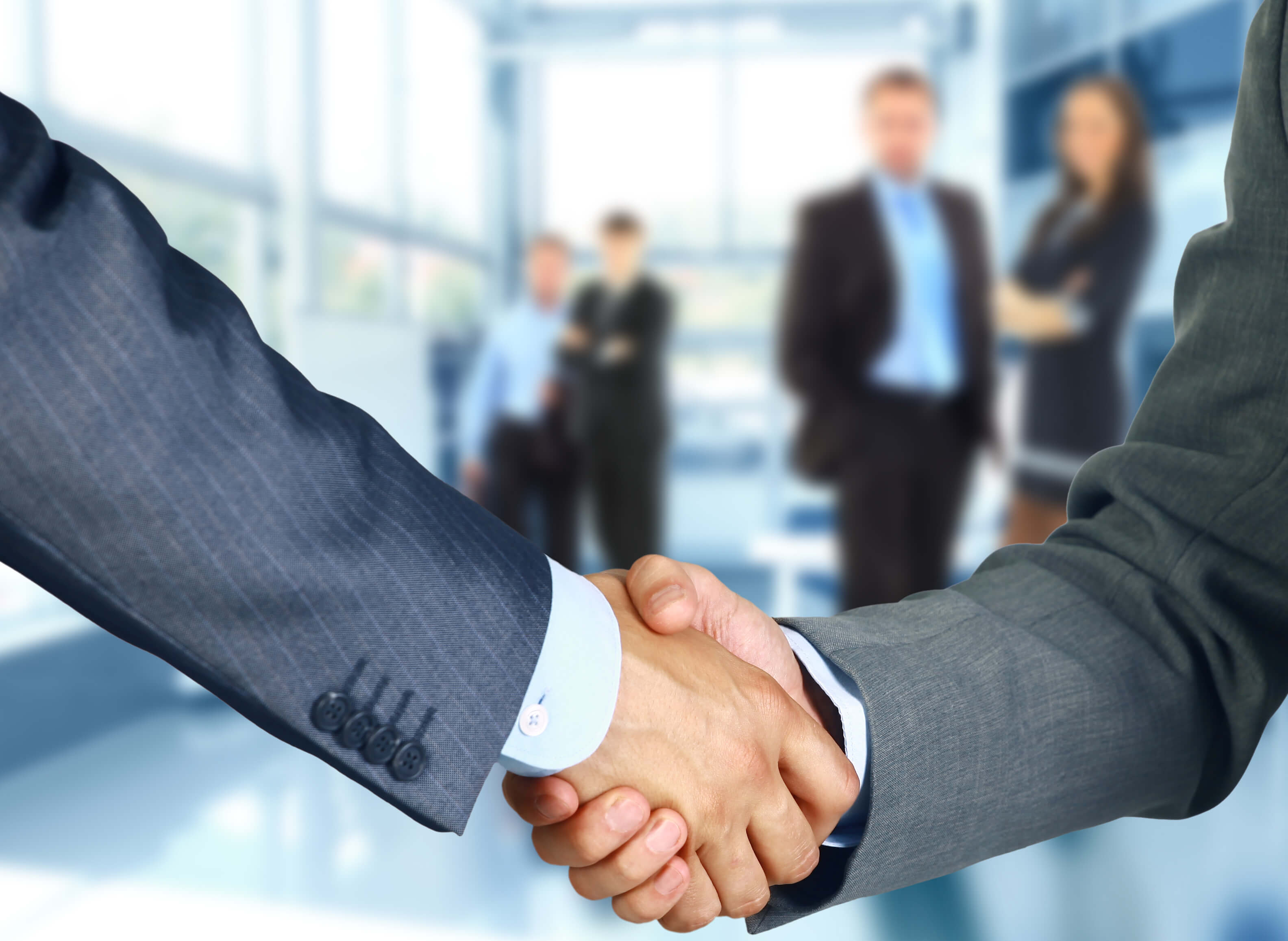 business-associates-shaking-hands-in-office